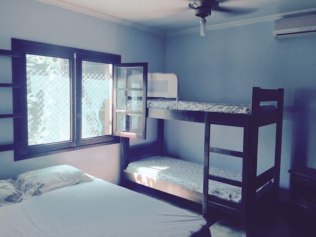 Quarto de hóspedes com cama de casal Queen,  triliche e equipado com ar-condicionado e ventilador de teto.