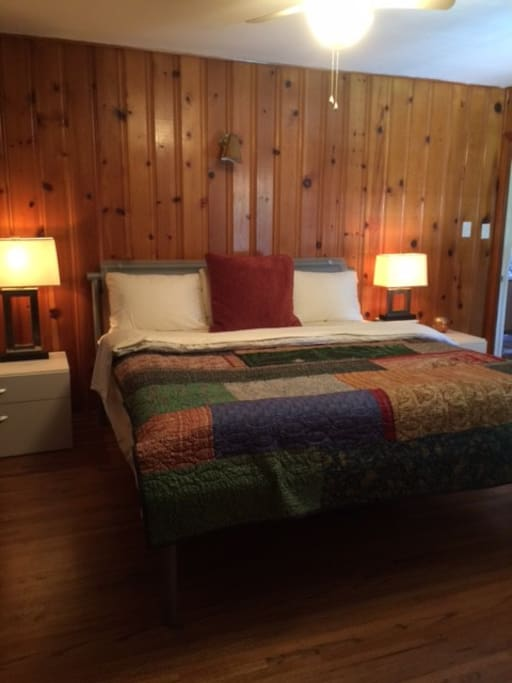 """""""Rustic Pine Room"""" has high end king bed, wood floors, private bathroom with shower and door to patio."""