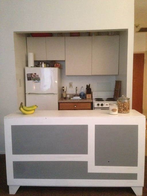 Efficiency kitchen with creative re-use island, refrigerator, electric stove, and more.