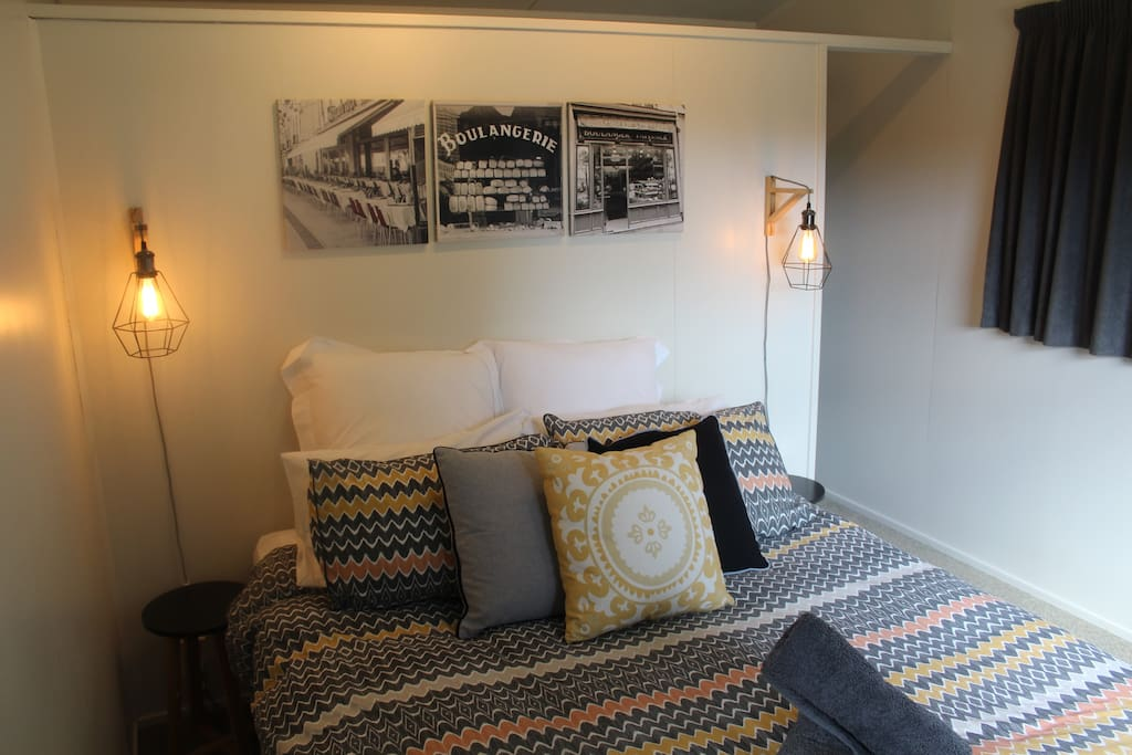 This double bedroom features a Queen size bed with a walk in wardrobe behind the bed.
