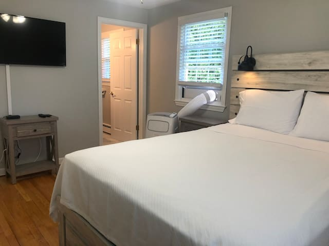 """master bedroom 1 with queen bed, large closet, half bath, and 40"""" HDTV"""