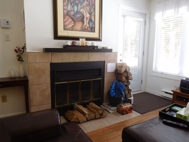 Wood burning fireplace in living room next to patio door.  Logs are supplied in limited quantities.