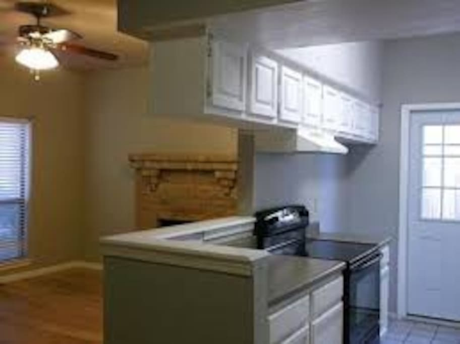 Shared kitchen includes electric stove, stainless steel  kitchen sink, dishwasher, microwave, and refrigerator.