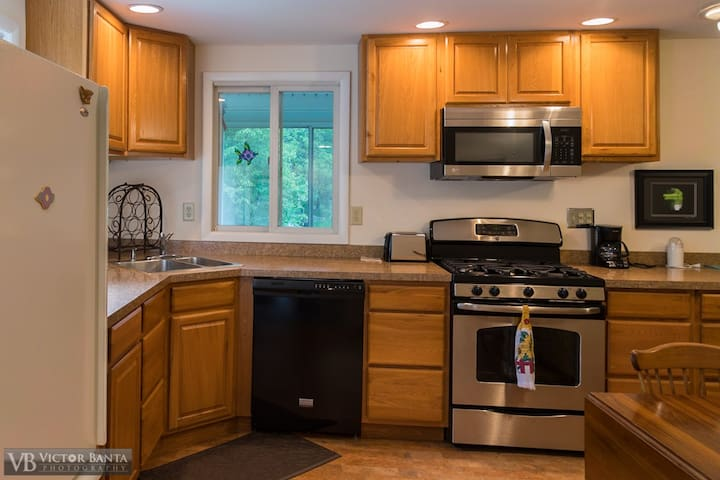The kitchen looks out at the Hi-land Lake and our private woods. 5 burner gas stove with oven, microwave, dishwasher, refrigerator.