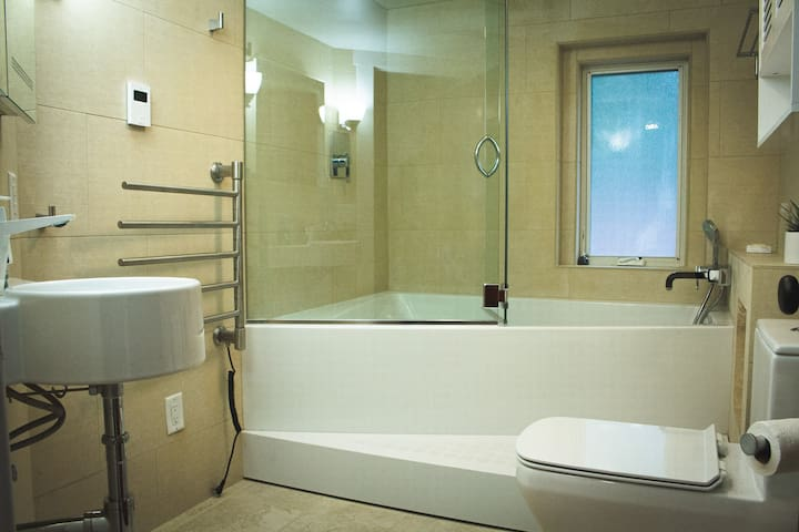 Second floor bathroom with double tub and two shower heads, heated towel rack and heated floor