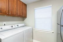 Laundry area a with full size washer and dryer. Laundry detergent and dryer sheets are provided.