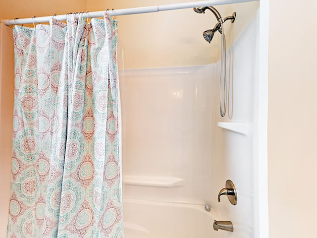 The guest bathroom is equipped with a tub/shower combination.