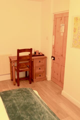 Your Bedroom: This is a basement room. It has a King Size bed with Ensuite shower, toilet, and sink.  Tea and Coffee in Room. Bedding, Towels, blanket provided and hangers in the wardrobe. Desk with draws and chair for you to sit and use your laptop.
