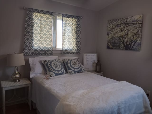This charming bedroom has a beautiful view of the backyard. It has a double bed.