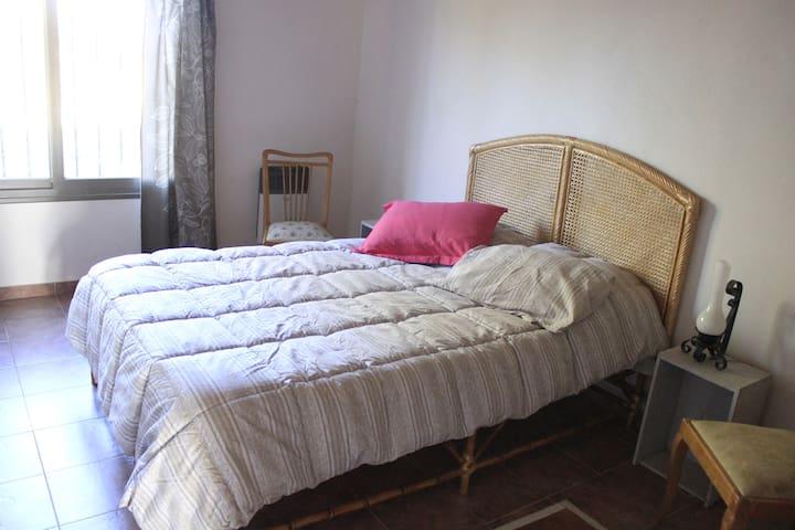 Dormitorio principal con cama 2 plazas, con mueble con estantes. Muy luminoso, con vista al jardín.