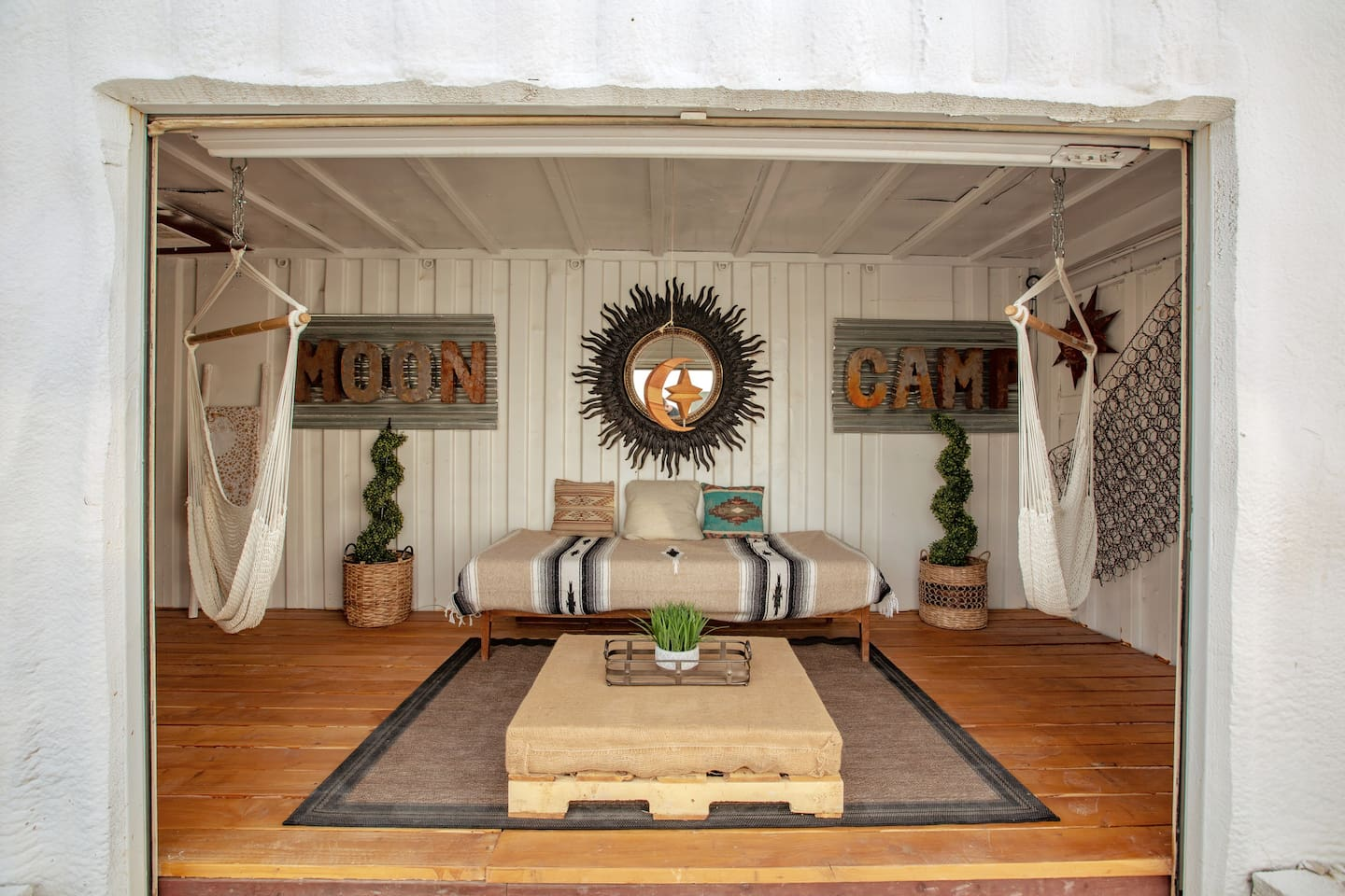 """Moon Camp's newly renovated """"Area 51"""" shipping container lounge living space equipped with a daybed and two swinging hammock chairs. Chill out amongst the stars!"""