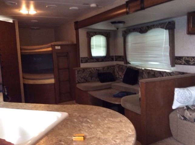 The slide out allows easy access to the double bunks and the dinette table drops for an additional sleeping area. Also creates a large working kitchen area.
