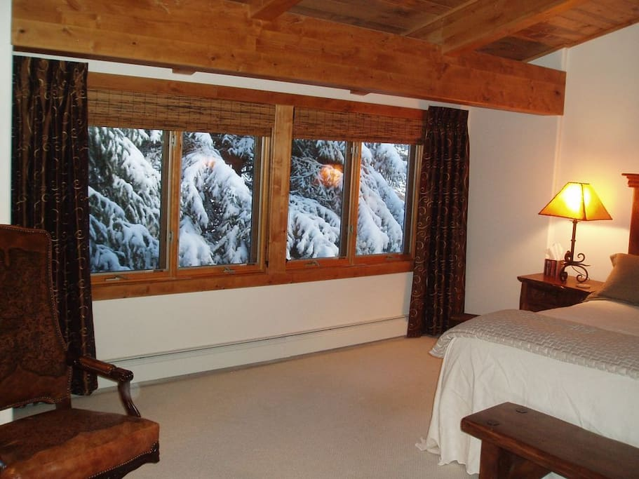 Creekside bedroom with king bed and wall of casement windows, view after a snow