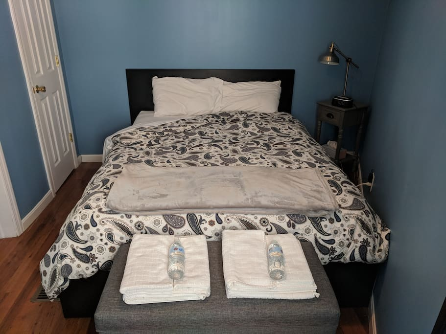 Queen sized bed, reading lamp, alarm clock and charging station