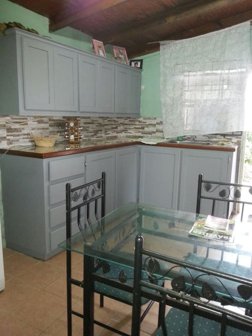 Modern self-contained kitchen with glass table, 4 chairs, stove and fridge