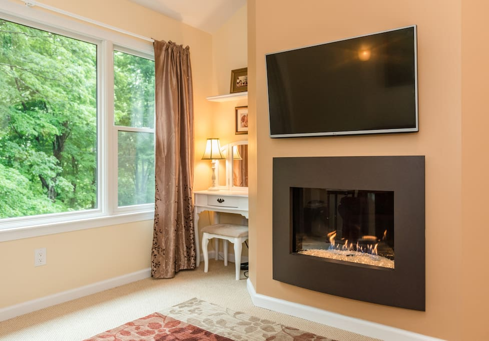 Master Bedroom sitting area with gas fireplace, flat screen TV, large picture window, and vanity
