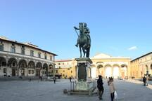 View of the whole Piazza SS. Annunziata, on the left Palazzo Budini Gattai, inside you can admire the famous Ammannati Garden, on the right Istituto degli Innocenti, in the middle there is the Cosimo De' Medici statue