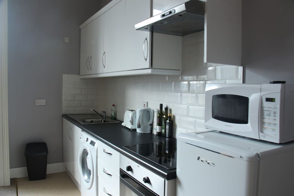 The kitchen is equipped with a microwave, stove, oven, and a kettle.