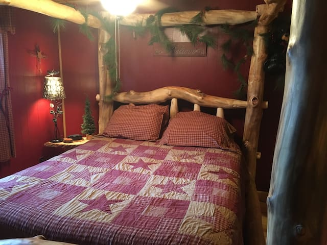 Master Bedroom with top of the line queen mattress with canopy log bed