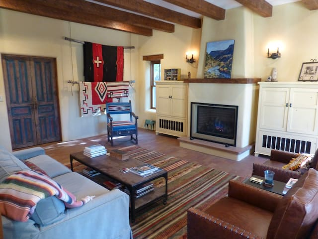 the great room features comfy leather chairs, a gas fireplace, antique doors to the guest wing and vintage native-american rugs