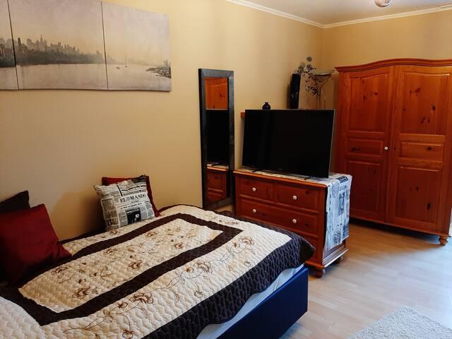 Das Boxspringbett mit TV-Kommode und Kleiderschrank.