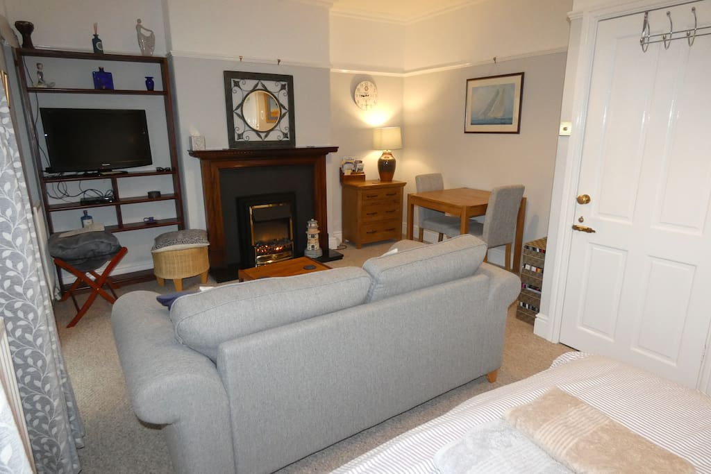 Lounge area, with electric fire, Wide screen TV with chromecast and DVD player.  We have a large selection of DVDs for you to choose from. The door on the right leads through the vestibule and bathroom.