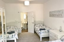 Family bedroom with one king size and two single beds.