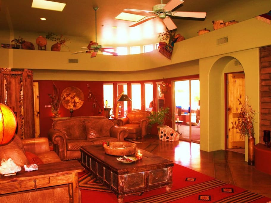 Main House living area has vaulted ceilings, custom decor, and opens out to the main patio