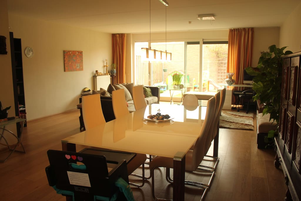 Dining table with glass top, hanging lights and leather chairs
