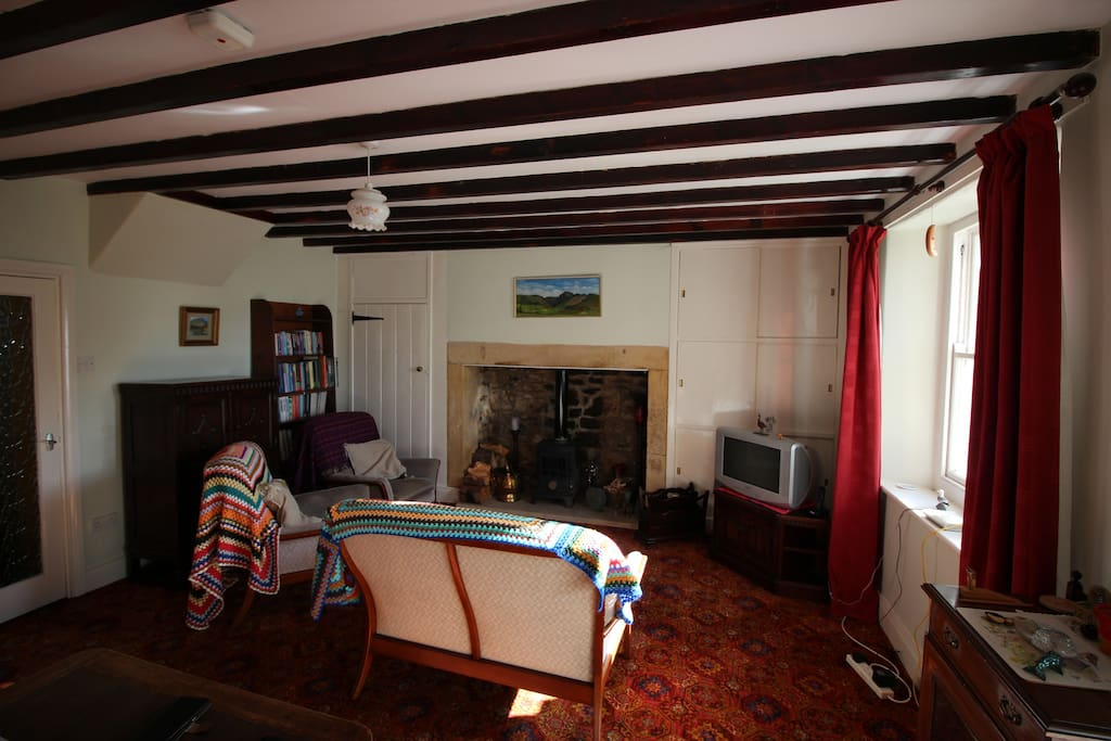 Original Inglenook fireplace with multifuel stove; original beamed ceiling and sash windows