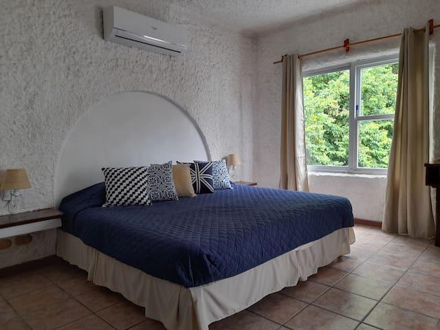 Amplia e iluminada habitación principal con confortable cama tamaño king size.