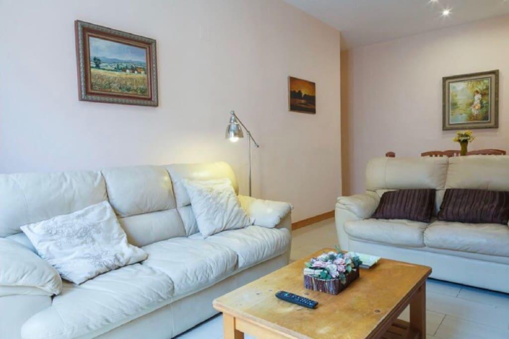 Salón grande con dos sofas y mesa de comedor para 6-7