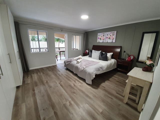 Master bedroom with king size bed and door out onto balcony.