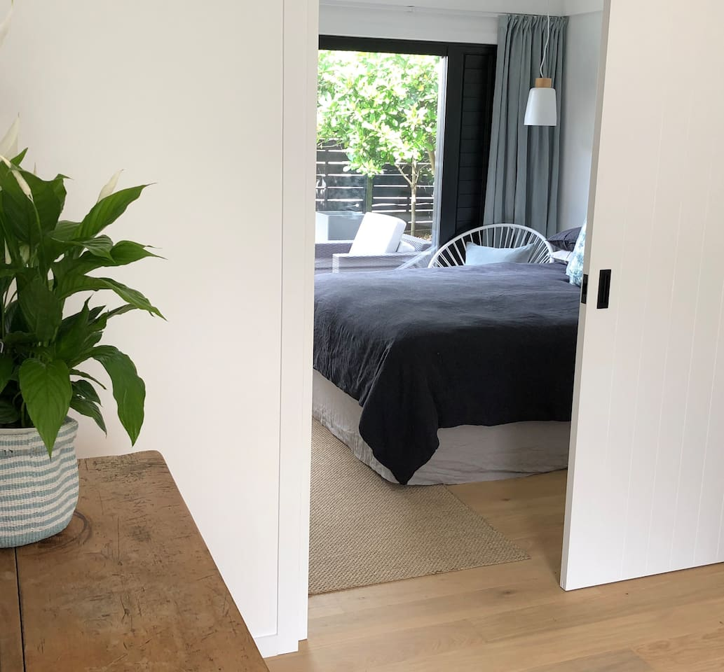 Looking through to the bedroom from the living space. Bedroom has direct access to tiled outdoor space and garden area. Cavity slider can be used to create two separate areas.