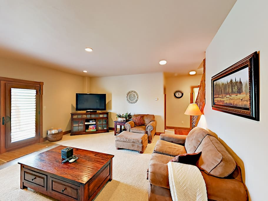 Spacious 2nd living room on the lower floor with plush seating and large flat screen TV.