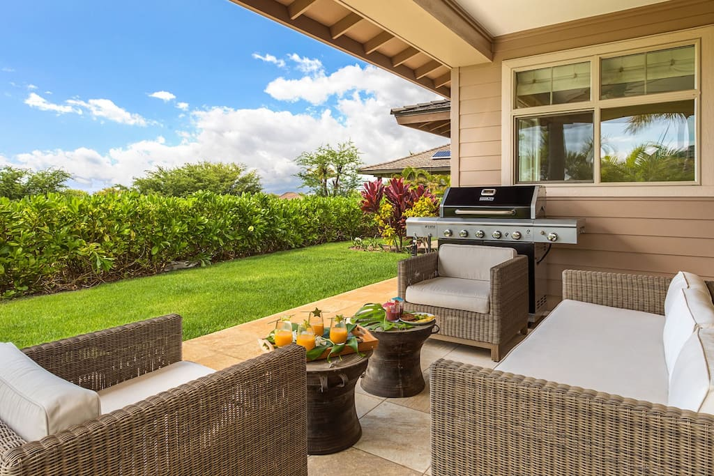 Outdoor lanai with Deluxe BBQ grill, seating, cafe tables, and grassy lawn area.