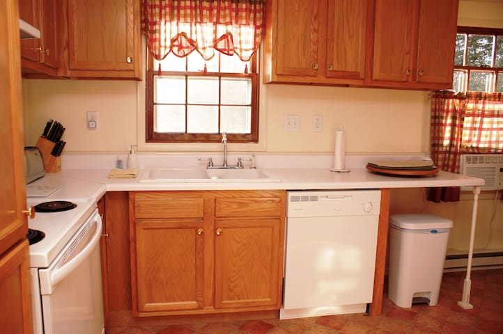 Kitchen with electric stove, large refrigerator/freezer, dishwasher, toaster, microwave, coffee pot, kettle, iced tea maker, and cooking and serving essentials and amenities.