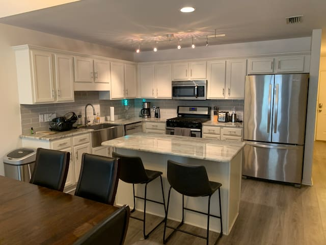 Large kitchen with gas stove, granite countertops, track led lighting, stainless refrigerator with ice maker, center island with bar stools, blender, toaster, coffee maker, juicer, automatic trash can.