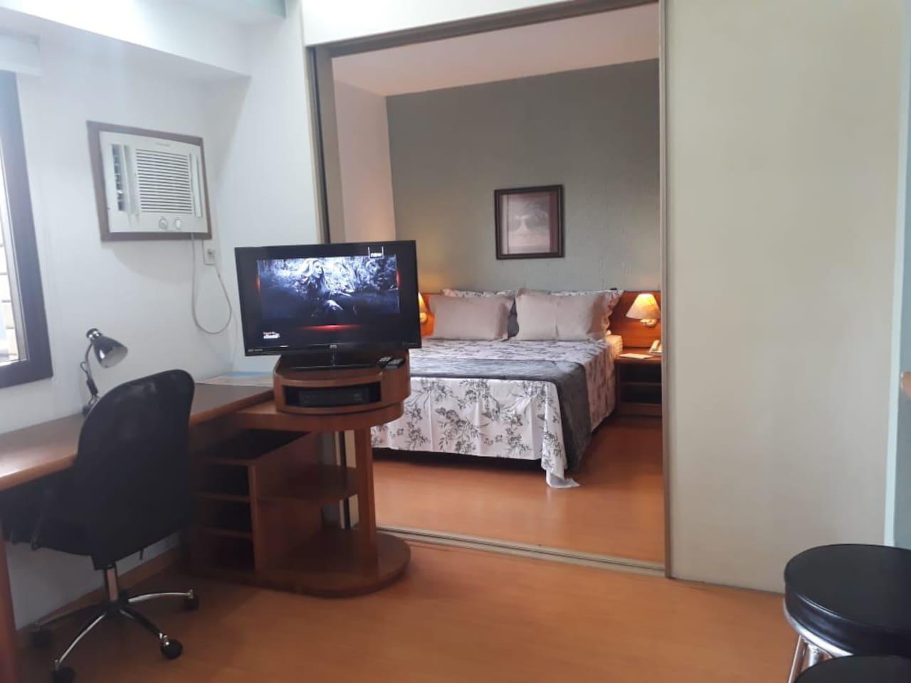 Sala conjugada com o quarto com divisórias moveis, ar condicionado, TV a cabo, rack giratório, internet exclusiva, mesa de trabalho, cadeira giratória.