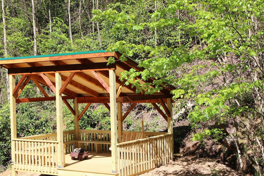 Pavilion with swing, benches and fire pit facing the waterfall