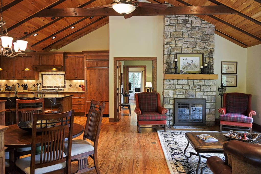 Featuring a vaulted ceiling with exposed beams, the open floor plan of the home allows for a large living room area, where the unique two-sided stone fireplace is ready to light. #fireplace
