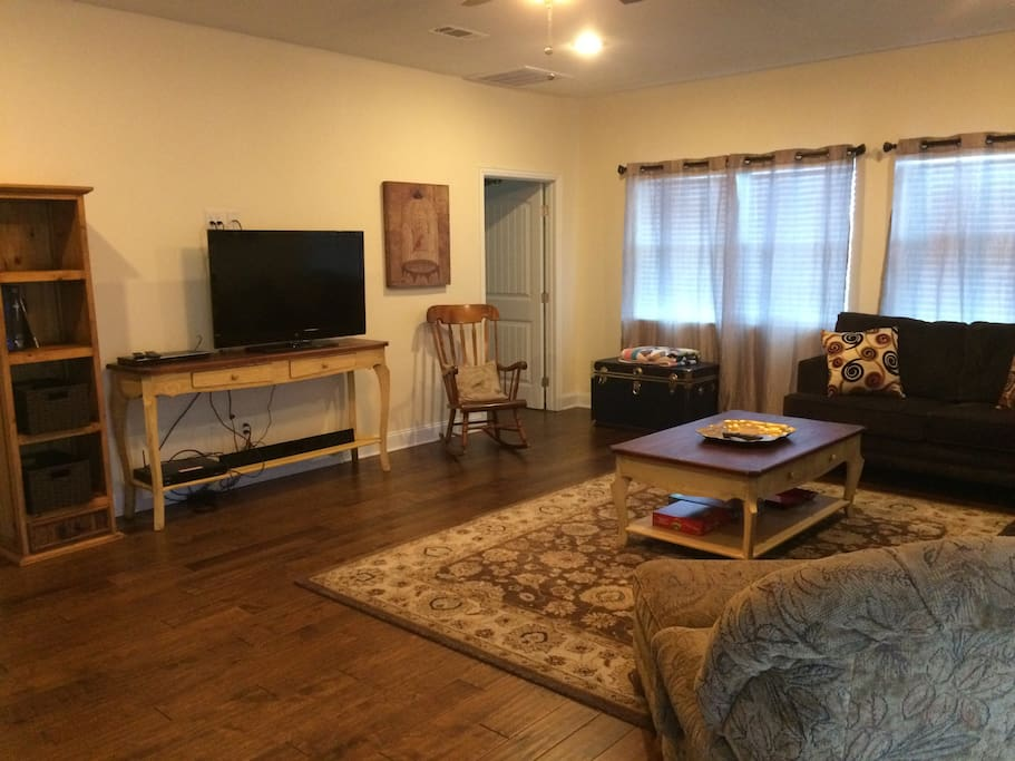 large spacious living area with love seat, large sofa and large chair/ottoman.