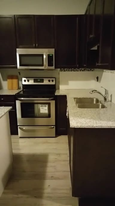 New kitchen, with new fridge, electric stove, microwave. Granite counter tops, laminate hardwood floor. Dishes & utensils.