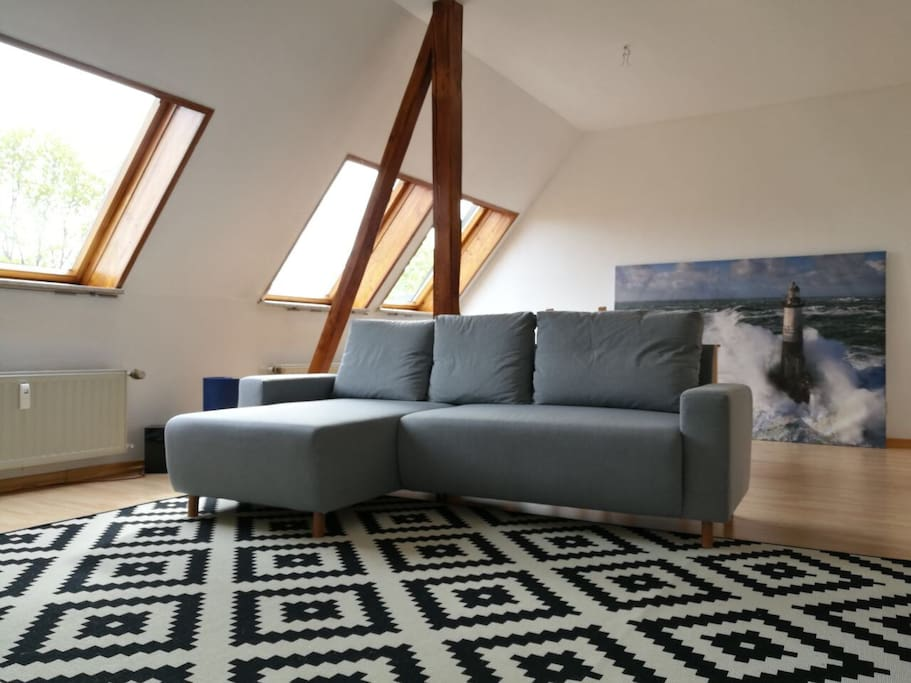 The spacious living room. Behind the sofa is the dinner table and seats.