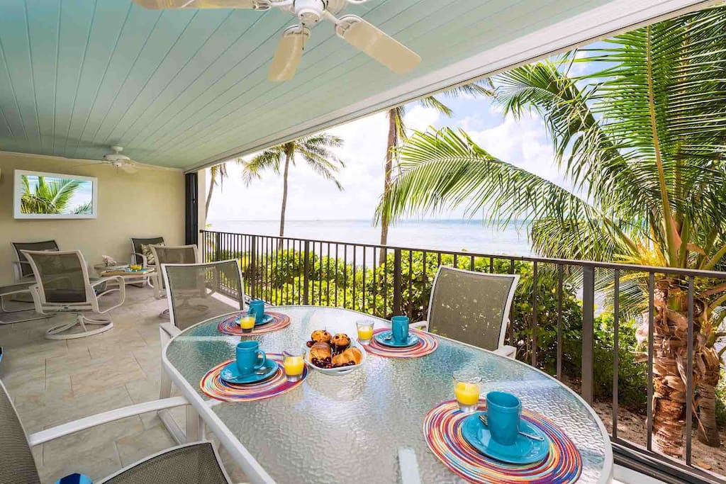 The balcony has an outdoor dining area and an amazing view of the water...