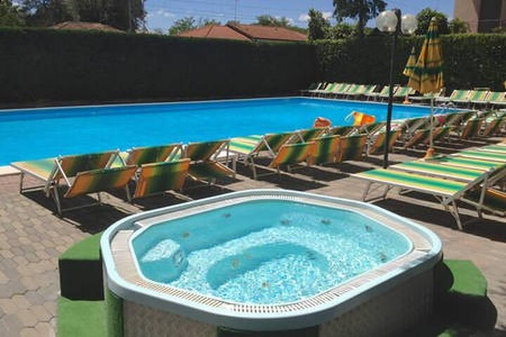 Piscina privata con vasca idromassaggio, lettini e servizi a disposizione dei nostri ospiti