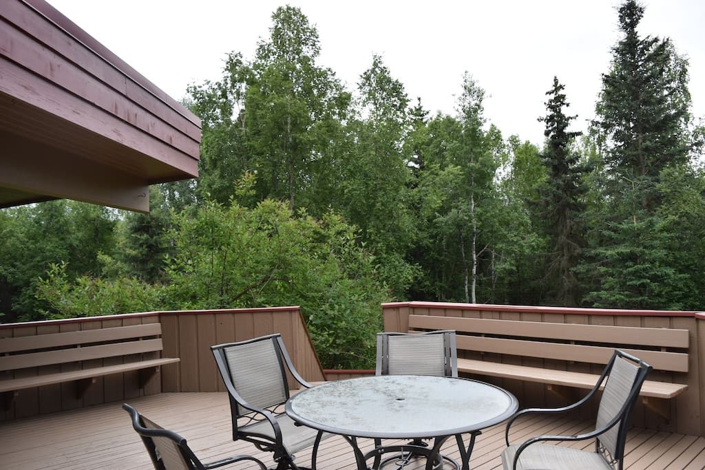 Open-air deck during the summer, overlooking the forested grounds