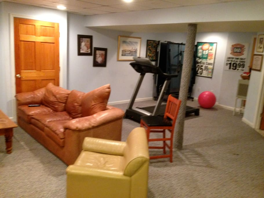another tv, treadmill, leather couch and chair
