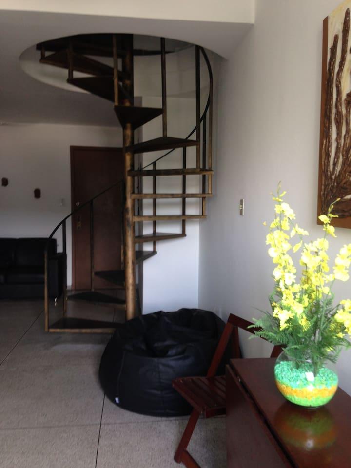 Sala e escada caracol com acesso ao banheiro e quarto.