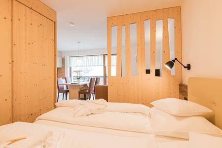 Beispiel Schlafzimmer mit Blick in Wohnraum und Ausblick auf die Berge